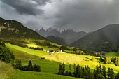 Sunlight through storm clouds over the Odle and village of Santa Magdalena, Val di Funes, South Tyrol, Dolomites, Italy
