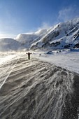 Man with arms raised standing in the windstorm on frozen coastal road, Barents Sea, Berlevag, Varanger Peninsula, Finnmark, Norway