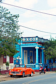Classic red car in front of a blue building in Viñales, Cuba