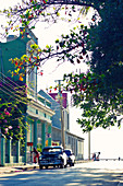 Street view with colourful buildings, flowers  and a classic car in Cienfuegos, Cuba