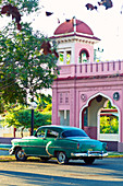 Classic green car in front of a pink gateway in Arabic style in Cienfuegos, Cuba