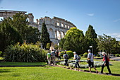 Tour group approaches Pula Arena Roman Amphitheater, Pula, Istria, Croatia, Europe
