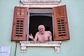 Friendly elderly man with bare chest looking out the window, Pula, Istria, Croatia, Europe