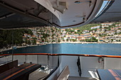 Reflection in window of cruise ship with view of town, Rabac, Istria, Croatia, Europe