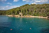 People swim in a beautiful bay near Kampor, Primorje-Gorski Kotar, Croatia, Europe