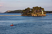 Man in sea kayak with lighthouse on island in the distance, Rab, Primorje-Gorski Kotar, Croatia, Europe