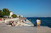 People relax on the beach promenade and listen to the sea organ, Zadar, Zadar, Croatia, Europe