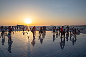 People gather on the magnificent monument to the sun at sunset, Zadar, Zadar, Croatia, Europe