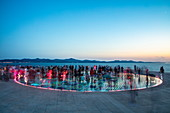People gather on the magnificent monument to the sun at dusk, Zadar, Zadar, Croatia, Europe