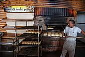 Baker with bread in the Macola restaurant, Korenika, Lika-Senj, Croatia, Europe