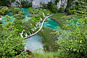 View of people on wooden plank path over pool with waterfalls, Plitvice Lakes National Park, Lika-Senj, Croatia, Europe