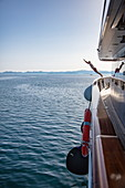 Man jumps from the deck of the cruise ship into the water to enjoy a swim in a pristine bay, near Kukljica, Zadar, Croatia, Europe