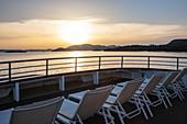 Liegestühle an Bord von Kreuzfahrtschiff bei Sonnenuntergang, nahe Kukljica, Zadar, Kroatien, Europa