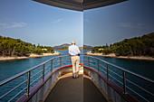 Spiegelung von Mann an Deck von Kreuzfahrtschiff mit Küste, Nationalpark Kornati-Inseln, Šibenik-Knin, Kroatien, Europa