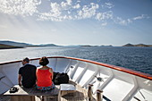 Couple relaxes on the bow of cruise ship with islands in the distance, Kornati Islands National Park, Šibenik-Knin, Croatia, Europe