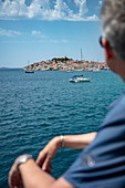 Sailboats moored in the harbor with the old town in the distance and blurred people in the foreground, Primosten, Šibenik-Knin, Croatia, Europe