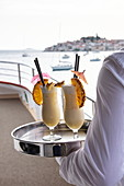 Detail of two cocktails on tray that waiter carries on board of cruise ship, Primosten, Šibenik-Knin, Croatia, Europe