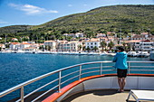 Woman stands on railing of cruise ship with view of town, Vis, Vis, Split-Dalmatia, Croatia, Europe