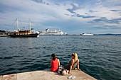 Zwei junge Frauen entspannen entlang der Strandpromenade mit Schiffen im Hafen, Split, Split-Dalmatien, Kroatien, Europa