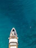 Luftaufnahme von Kreuzfahrtschiff mit Mann der neben dem Bug im Wasser schwimmt, nahe Kampor, Primorje-Gorski Kotar, Kroatien, Europa