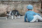 Sitting child watches the cat walking past in Marbella, Spain