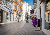 Old Spanish woman is walking on a street in Marbella, Spain