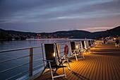 Stühle auf Sonnendeck von Flusskreuzfahrtschiff  während einer Kreuzfahrt auf dem Rhein in der Abenddämmerung, Rüdesheim am Rhein, Hessen, Deutschland, Europa