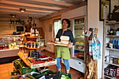 Friendly woman with cheese for sale in the farm shop at the ecological farm Der Berghof, Schöllkrippen, Kahlgrund, Spessart-Mainland, Franconia, Bavaria, Germany, Europe