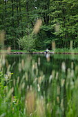 Man relaxes on the bank of a pond with grasses in the foreground, Kleinostheim, Spessart-Mainland, Franconia, Bavaria, Germany, Europe