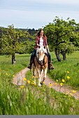 Young woman rides horse along field path through lush spring meadow, Heimbuchenthal, Räuberland, Spessart-Mainland, Franconia, Bavaria, Germany