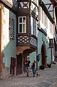 Young couple with dog strolls along historical market square Schnatterloch, Miltenberg, Spessart-Mainland, Franconia, Bavaria, Germany, Europe