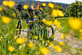 Man rides a bicycle for paraplegics on a dirt road through lush spring meadow, Heimbuchenthal, Räuberland, Spessart-Mainland, Franconia, Bavaria, Germany, Europe