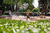Zwei Jungen haben Spaß und bespritzen sich mit Wasser auf einem städtischen Spielplatz, Tauberbischofsheim, Baden-Württemberg, Deutschland, Europa
