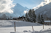 Farmhouse in snowy winter landscape in front of mountain panorama, Germany, Bavaria, Oberallgäu, Oberstdorf