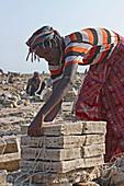 Äthiopien; Region Afar; Danakil Wüste; Danakil Senke; Arbeiter auf den Salzpfannen; lösen und bearbeiten der Salzplatten in mühevoller Handarbeit; rechteckige Salzplatten werden zu Paketen geschnürt