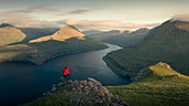 Couple at Hvithamar near the town of Gjogv on the Faroe island of Eysturoy with a panoramic view of the fjord at sunset