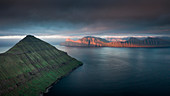 View from Hvithamar near the town of Gjogv on the Faroe island of Eysturoy with a panoramic view over the fjord towards Kalsoy at sunset