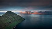 Ausblick vom Hvithamar nahe dem Ort Gjogv auf der Färöer Insel Eysturoy mit Panoramablick über Fjord Richtung Kalsoy bei Sonnenuntergang\n