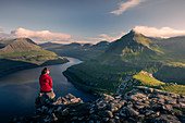 Woman sitting at Hvithamar near Gjogv on the Faroe island of Eysturoy with a panoramic view of the fjord