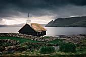 Kirche der Gemeinde Funningur auf Insel Eysturoy unter dramatischen Wolken, Färöer Inseln\n