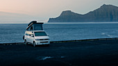 White VW camper van with pop-top roof in Gjogv on Eysturoy by the sea, view of Kalsoy Island at sunset, Faroe Islands