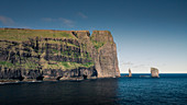 Risin og Kellingin rocks on Faroe Islands during the day with sun and blue sky
