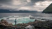 Woman on the coast of Gjogv with waves, Faroe Islands