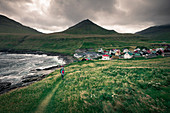 Man walks on path in front of the village of Gjogv on Eysteroy, Faroe Islands