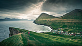 Woman hikes to village Gjogv on Eysteroy with gorge, sea and mountains, Faroe Islands