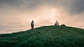 Woman hikes to lighthouse on Kalsoy Island, Faroe Islands