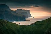Man hiking on cliff on Kalsoy island, cliff and rocks of Eysteroy in background in sunset, Faroe Islands