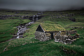 Huts with a grass roof and waterfall in Saksun village on Streymoy Island, Faroe Islands
