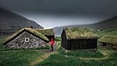 Mann in roter Jacke vor Hütten mit Grasdach im Dorf Saksun auf der Insel Streymoy, Färöer Inseln\n