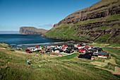 Woman hiking with a view of Tjørnuvík village on Streymoy on Faroe Islands by day